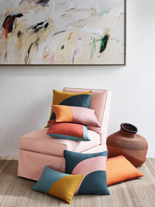 different coloured cushions on pink chair and styled interior behind